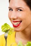 Portrait of a young woman, smiling and eating lettuce Royalty Free Stock Photos