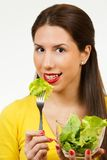 Portrait of a young woman, smiling and eating lettuce Stock Image