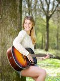 Portrait of a young woman smiling with guitar outdoors Stock Photo