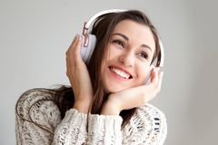 Smiling young woman listening to music with headphones. Portrait of young woman smiling and listening to music with headphones Royalty Free Stock Photos