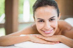 Portrait of young woman smiling while resting on massage table Stock Photography