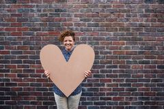 Young woman smiling and holding a large heart outside Stock Images