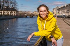 Portrait of a young woman smiling on a Sunny day on a spring street by the river royalty free stock photography