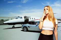 Portrait of young woman smoking cigarette with car and airplane in the background Royalty Free Stock Photo