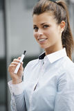 Portrait of young woman smoking electronic cigarette Royalty Free Stock Photo