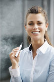 Portrait of young woman smoking electronic cigarette outdoor off Stock Photography