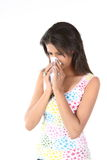 Portrait of a young woman sneezing. Indian teenage girl with tissue paper Stock Image