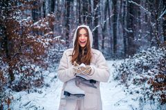 Portrait of a young woman in snow trying to warm herself. Winter woman happy. Sensual brunette winter girl posing and stock images