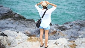 Portrait of young woman stand on the rock with sea, blue sky and cloud at Koh Sichang in Thailand. royalty free stock photos