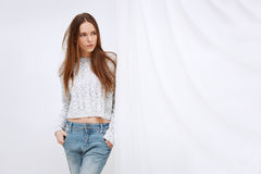 Portrait of young woman standing against curtains. Royalty Free Stock Images