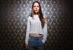Portrait of young woman standing against dark wall. Royalty Free Stock Photos