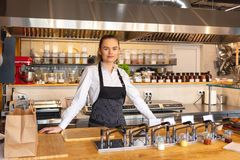 Portrait of young woman standing behind kitchen counter in small eatery. Restaurant owner wearing apron looking confident at camera smiling royalty free stock image