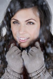 Portrait of a young woman standing in the falling snow, smiling Royalty Free Stock Image