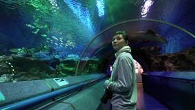 Portrait of young woman standing on moving walkway going through tunnel in oceanarium. Girl enjoying view of magnificent