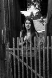 Portrait of a young woman standing near a wooden fence in the village. Black and white portrait of a young woman standing near a wooden fence in the village Royalty Free Stock Image