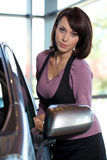 Portrait of young woman standing by new car in showroom Royalty Free Stock Images