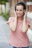 Portrait of young woman standing outdoors, listening to music Royalty Free Stock Images