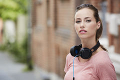 Portrait of young woman standing outdoors, wearing headphones Stock Images