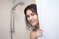 Portrait of young woman standing in shower with curtain Royalty Free Stock Photos