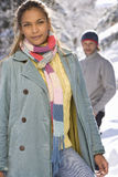 Portrait of young woman standing in snow, man in background royalty free stock images