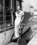 Portrait of a young woman standing on steps of a boat and smiling Stock Images