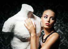 Portrait of a young woman with a statue. Portrait of an attractive young lady with a statue. The image is taken on a retro background Stock Images