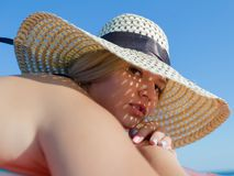 Portrait of young woman in straw hat. With sunlight through holes on her face. Attractive young woman in straw hat putting his head on the folded hands looking Royalty Free Stock Images
