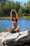 Portrait of a young woman stretching by a lake Stock Photography