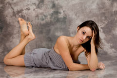 Portrait of a young woman in studio, lying on the floor Royalty Free Stock Photos