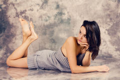 Portrait of a young woman in studio, lying on the floor Stock Photos