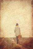 Portrait of young woman with suitcase and dog Stock Photo