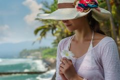 Portrait of young woman in summer hat with big colorful flowers is smiling and holding white tropical flower on the ocean beach royalty free stock photos