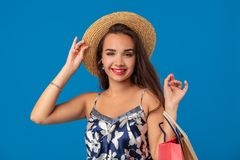 Portrait of a young woman in summer hat holding shopping bags and looking at the camera isolated over blue background. The concept of shopping royalty free stock photo