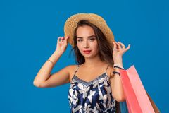 Portrait of a young woman in summer hat holding shopping bags and looking at the camera isolated over blue background. The concept of shopping stock images