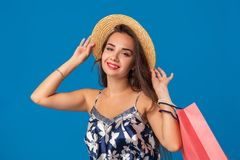 Portrait of a young woman in summer hat holding shopping bags and looking at the camera isolated over blue background. The concept of shopping royalty free stock photography