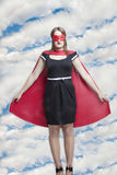 Portrait of young woman in superhero costume against cloudy sky Stock Photography