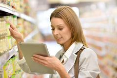 Portrait of young woman in supermarket using tablet. Woman in supermarket checking shopping list on tablet Royalty Free Stock Photography