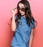 Portrait of a young woman surprised looking at something over sunglasses. Beautiful dark wavy hair, a denim shirt. Pink background Stock Photography