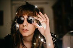 Portrait of a young woman surrounded by led lights touching sunglasses royalty free stock image