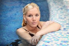 Portrait of a young woman in swimming pool. Portrait of a young blond woman in swimming pool stock photo