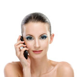 Portrait of young woman talking on. Portrait of young adorable woman talking on telephone against white background royalty free stock photography