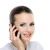 Portrait of young woman talking on. Portrait of young adorable smiling woman talking on telephone against white background royalty free stock image