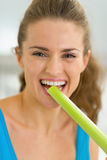 Portrait of young woman tasting fresh celery Royalty Free Stock Images