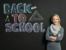 Portrait of a young woman, teacher in front of a blackboard Royalty Free Stock Images