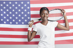 Portrait of young woman with tennis racket against American flag Royalty Free Stock Image