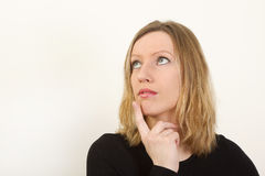 Portrait of young woman thinking and looking up Royalty Free Stock Photography