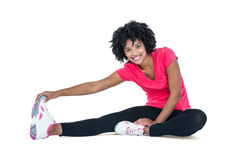 Portrait of young woman touching toes while exercising. Against white background Royalty Free Stock Images