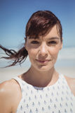 Portrait of young woman with tousled hair at beach. Portrait of young woman with tousled hair standing at beach during sunny day Royalty Free Stock Image