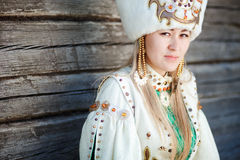 Portrait of a young woman in traditional dress. Portrait of a young woman in traditional dress of the peoples of South Siberia, against the wall of timber Stock Photos