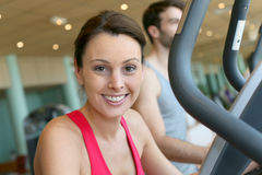 Portrait of a young woman training on cardio equipement. Woman in fitness club using cardio equipment Stock Image